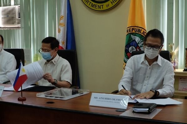 DOH secretary and TMP president signing an agreement