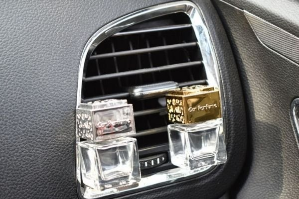 Two car air fresheners attached to an a/c vent