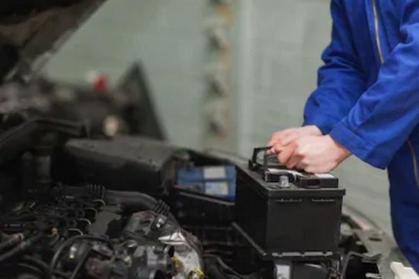 A man holding onto a car battery