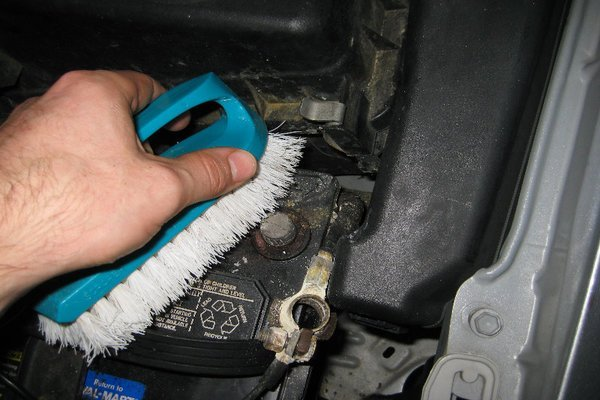 A person brushing his/her car battery terminal