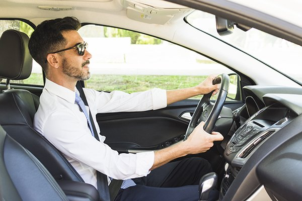 A picture of a man wearing sunglasses while driving.