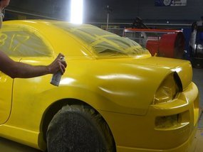 A painter painting a car yellow