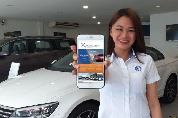A saleslady holding a phone with the AC Motor webpage in it