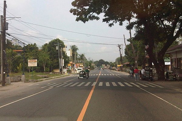 A picture of a road with a single solid yellow line.
