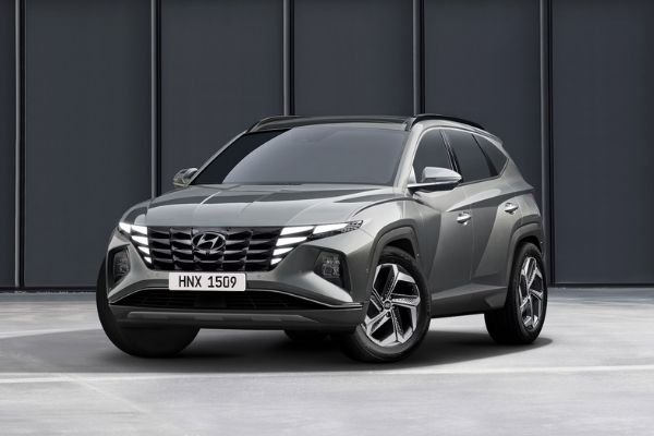 A picture of the new Tucson near some buildings.