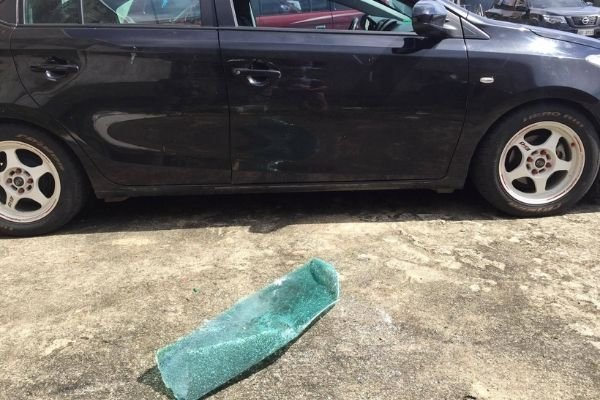 A picture of a car with damaged window caused by exploding bottle of alcohol.