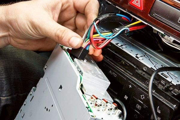A man pulling out a car stereo
