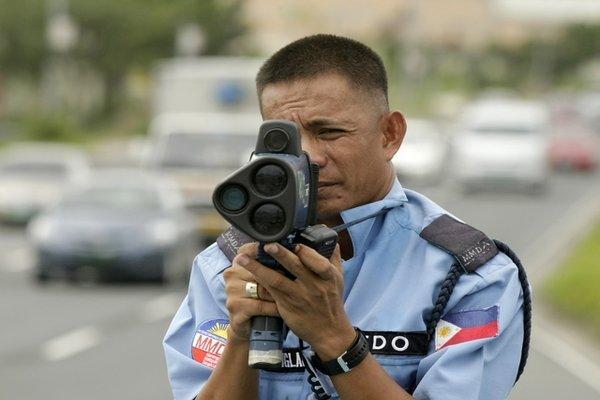 A man holding a speed gun