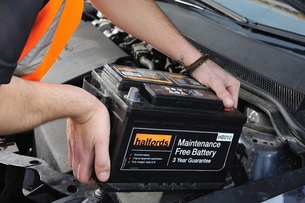 A picture of a man installing a new car battery.