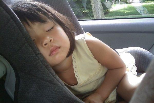A girl sleeping in a car