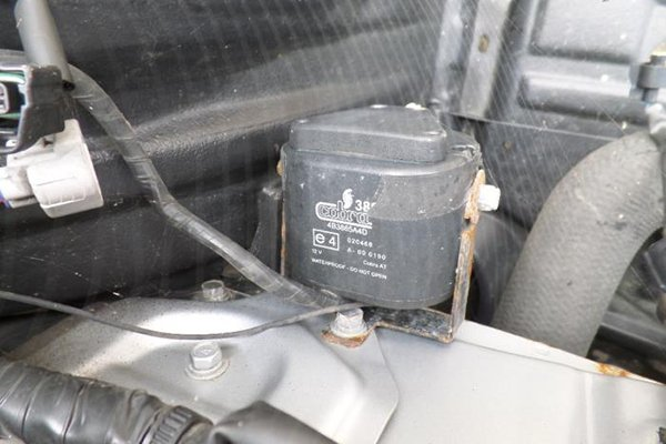 A picture of a car alarm siren mounted in the engine bay.