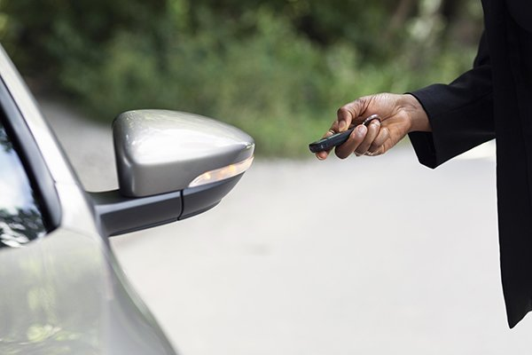 A picture of a man pressing a key fob.