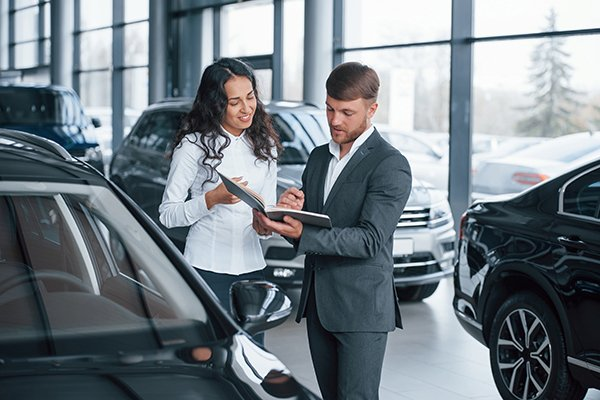 A picture of a woman buying a car.