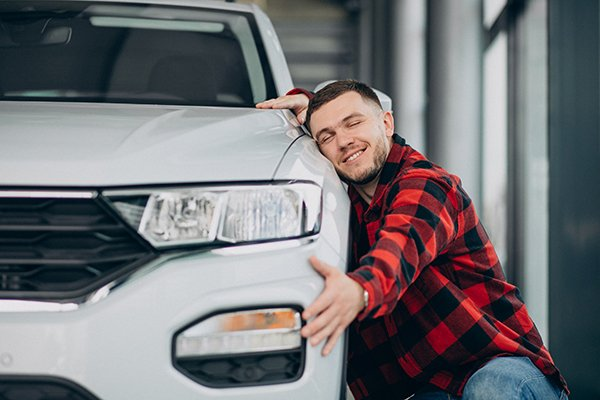 A picture of a man hugging a car.