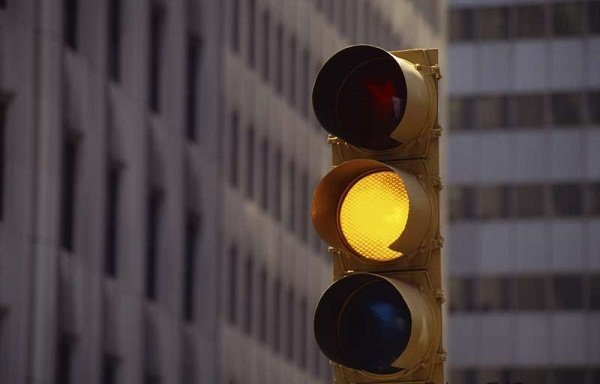 A picture of a blinking yellow traffic light