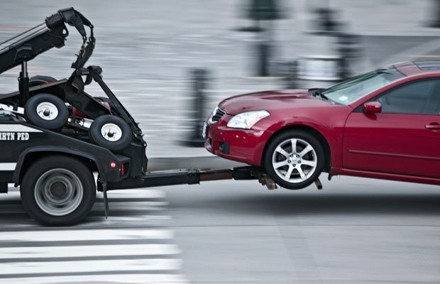 A picture of a tow truck towing a car