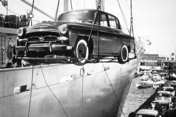 A picture of a 1st-gen Crown being unloaded from a cargo ship