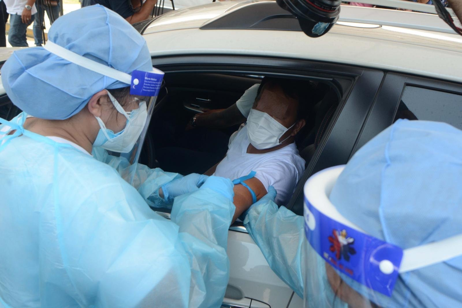 Medical personnel taking sample from patient