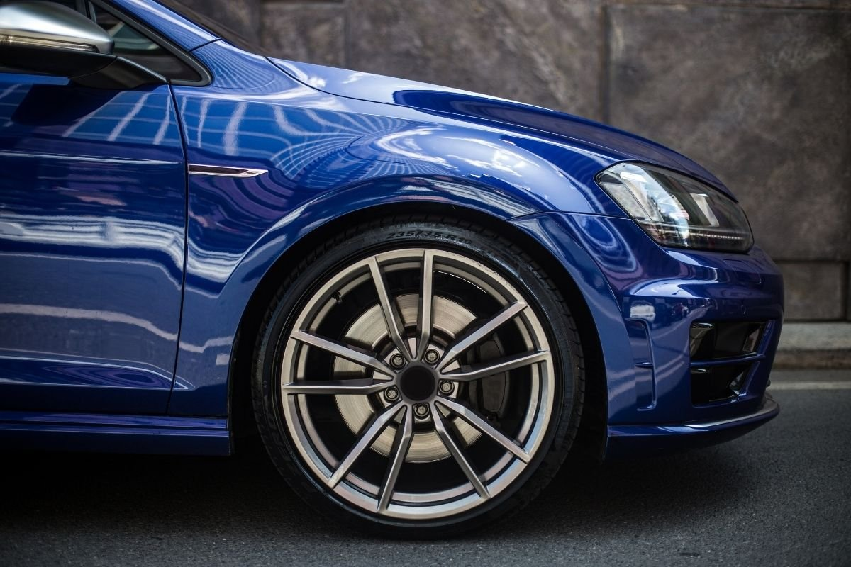 A picture a blue sedan and its wheels