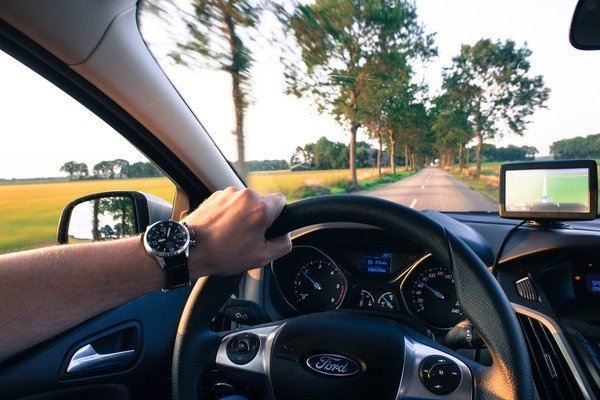 Person holding a steering wheel with one hand