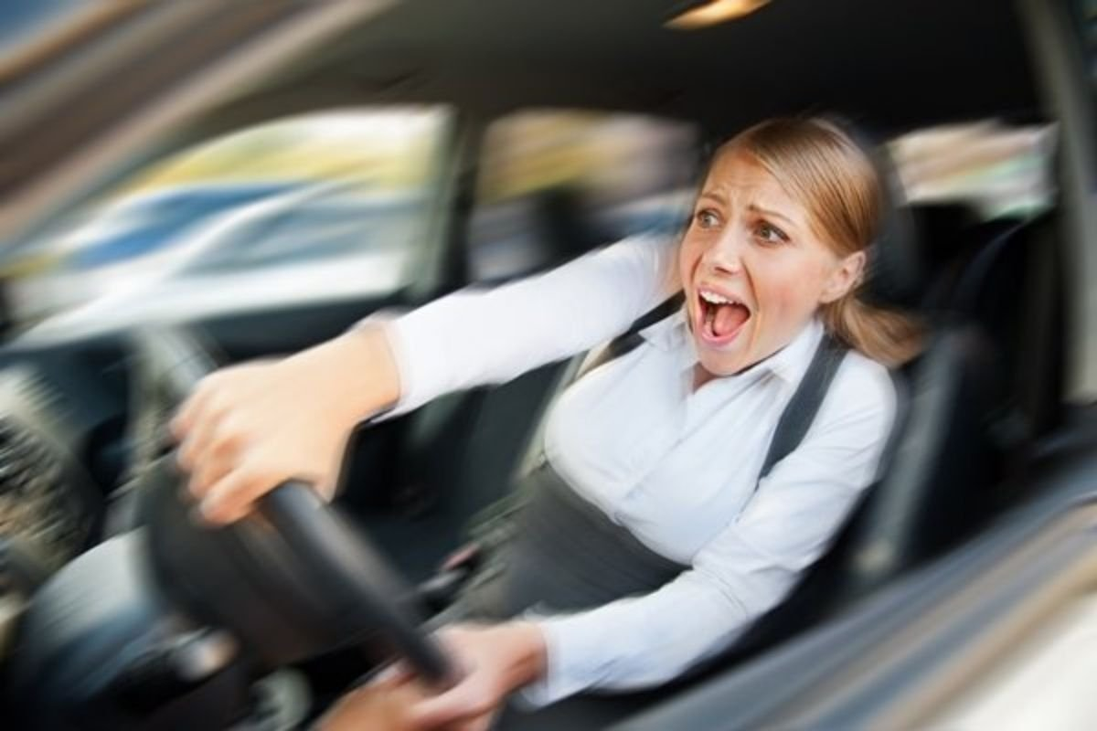 A picture of a woman grimacing while driving a car