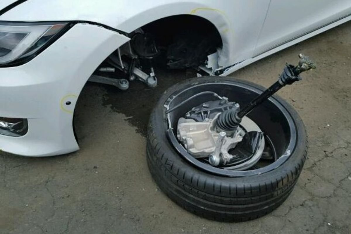 A picture of a parked Tesla with a broken tie rod