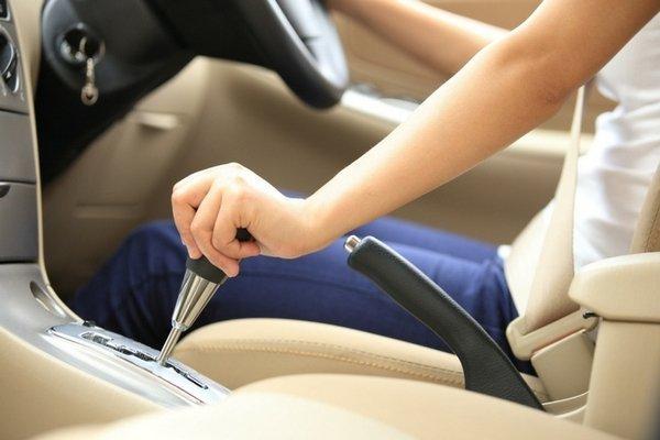 A driver shifting a gear selector