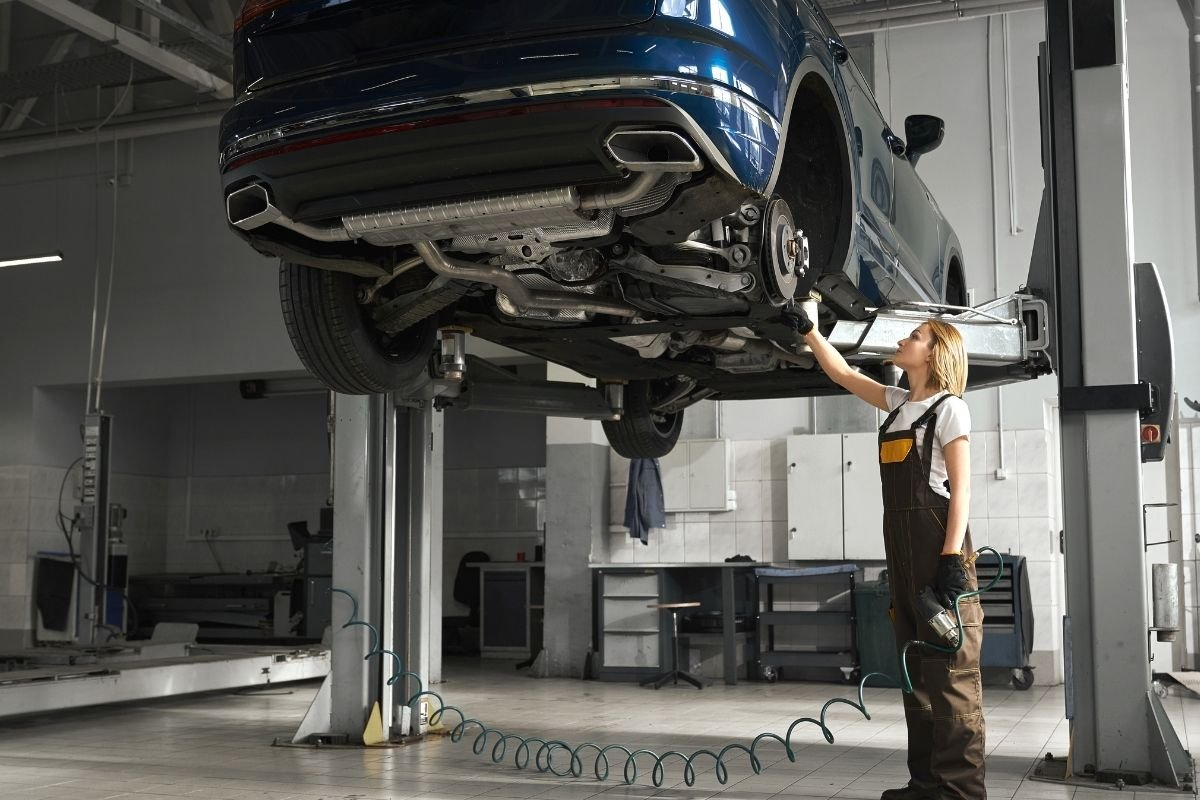 A picture of a mechanic lifting a car using a hydraulic lifter