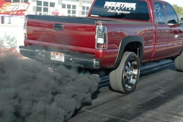 A red truck emitting black smoke