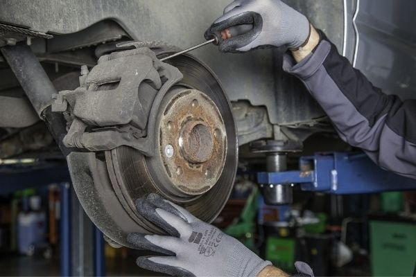 Man servicing a braking caliper