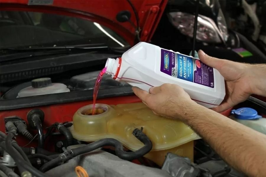 A picture of a man refilling a car's coolant