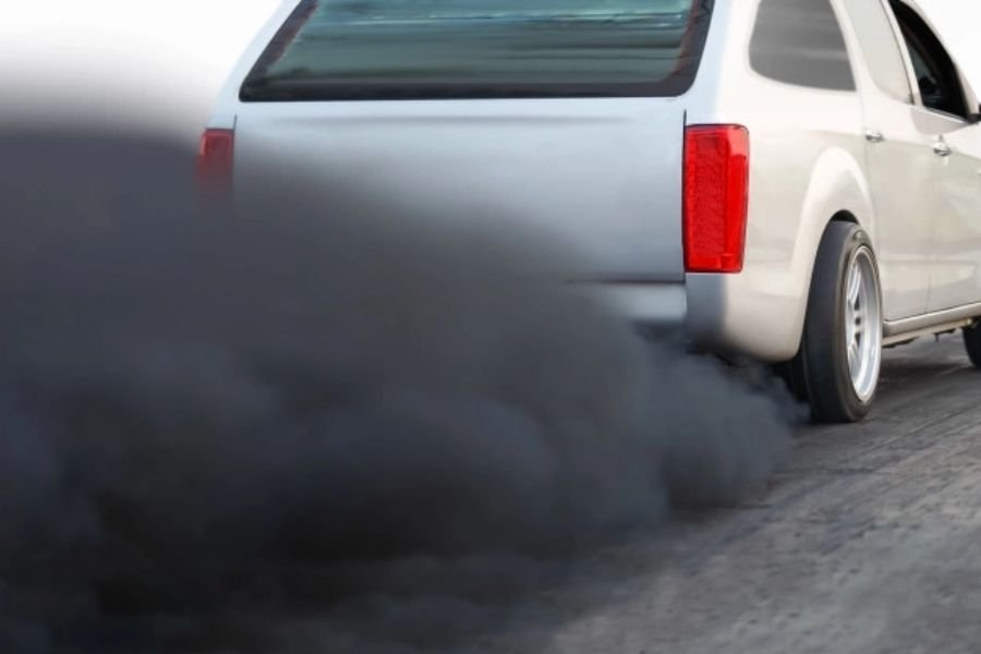 A picture of a pick-up truck spewing dark exhaust gases