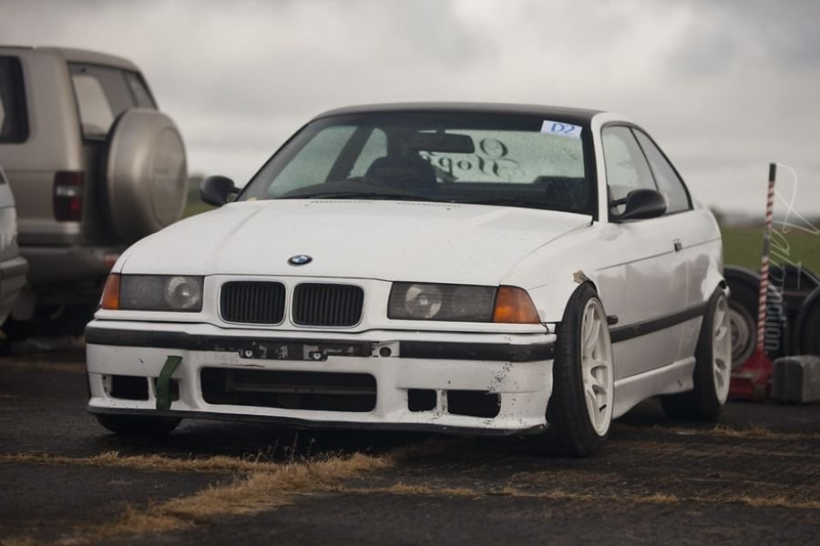 A picture of the a BMW E36 parked on a drift track's parking lot