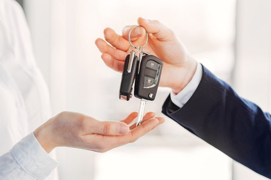 A picture of the man handing keys over to another man