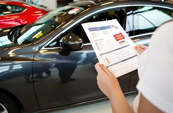 a woman holding a vehicle history report