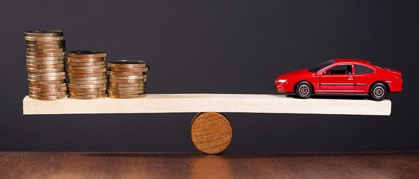 A long plank balanced in the middle on a fixed support, on one end is a car and the other are stacks of coins